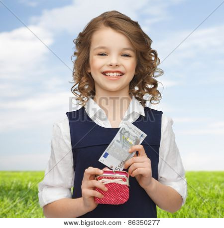 finances, childhood, people and savings concept - happy little girl with purse and paper euro money over blue sky and grass background