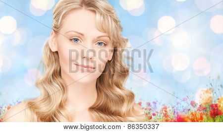 beauty, people, hair care and health concept - beautiful young woman face with long wavy hair over blue lights background