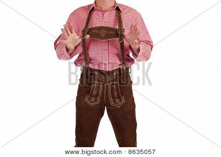 Bavarian man with oktoberfest leather trousers stands casual.