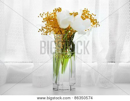 Beautiful spring bouquet in vase on windowsill