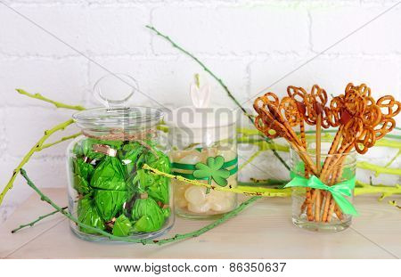 Sweets in jars for St Patrick Day on table on brick wall background