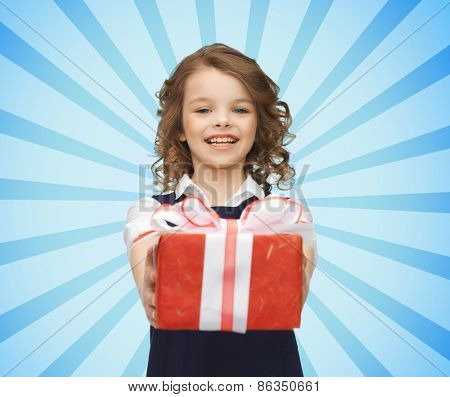 people, holidays, charity and children concept - happy girl with red gift box over blue burst rays background