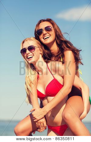 summer vacation, holidays, travel, friendship and people concept - two smiling young women on beach
