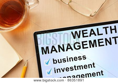 Tablet with words wealth management.