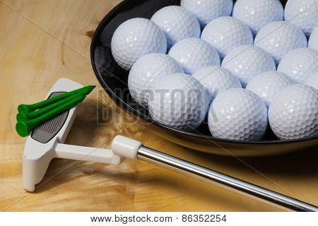 Black Ceramic Bowl Full Of Golf Balls And Putter