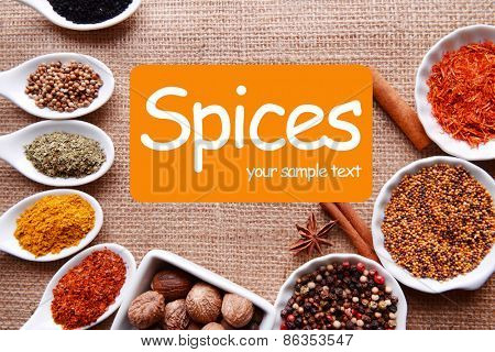 Different kinds of spices in ceramics bowls and spoons on sackcloth background