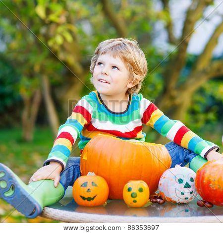 Little Kid Boy Making Jack-o-lantern For Halloween In Autumn Garden