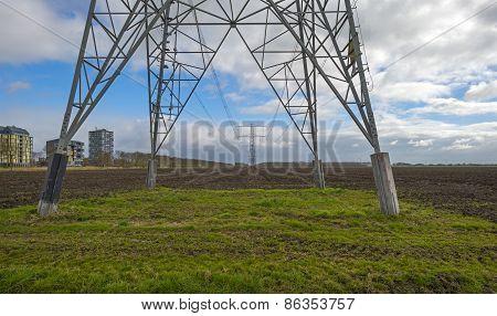 Power line in a plowed field near a city in spring
