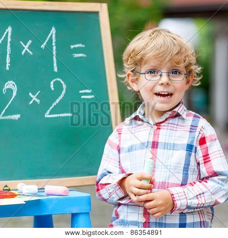 Cute Little Kid Boy With Glasses At Blackboard Practicing Mathematics