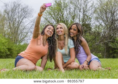 Three young women taking selfies and enjoying a day at the park