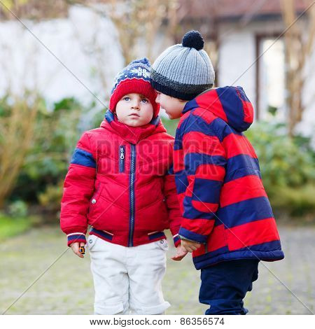 Two Little Sibling Boys In Red Jackets And Winter Hats Talking Together