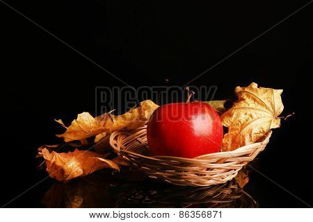 Apple in wicker basket with dried leaves on black background