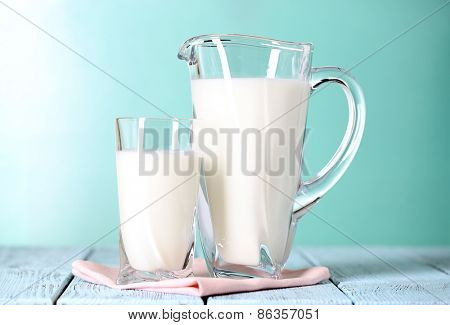 Pitcher and glass of milk on wooden table on blue background