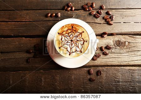 Cup of latte on wooden table, top view