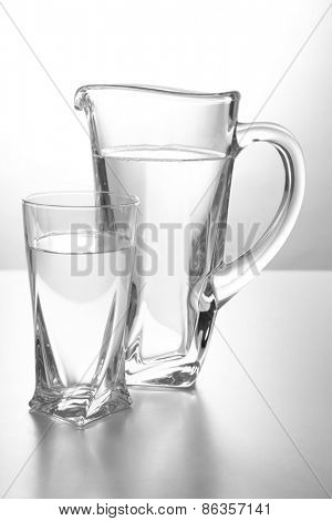 Glass pitcher and glass of water isolated on white