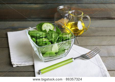 Glass bowl of green salad with cucumber and spinach on wooden background