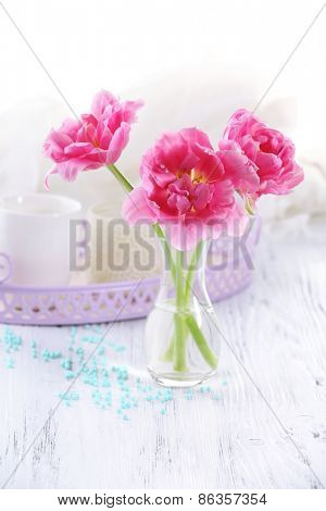 Pink tulips in glass vase on wooden table, closeup