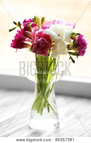 Beautiful spring flowers in glass vase on windowsill background