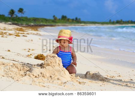 cute little girl building sandcastle on the beach