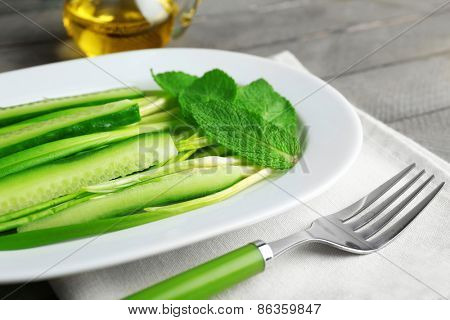 Green salad with cucumber and wild leek on wooden table, closeup