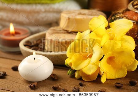 Composition with yellow flower and spa treatment on wooden table background