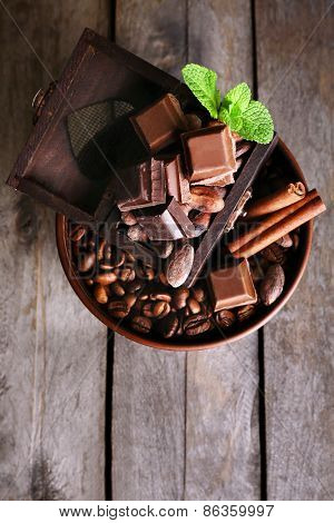 Still life with set of chocolate  and coffee beans on wooden background