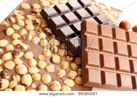 Black and milk chocolate bars with hazelnuts close up
