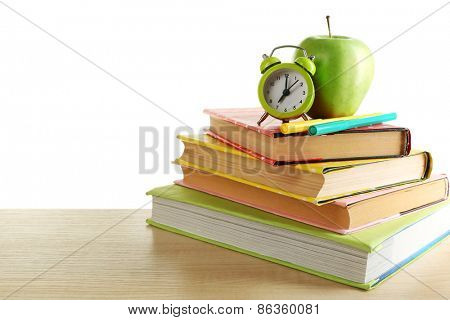 Books, alarm clock and apple on desk, isolated on white