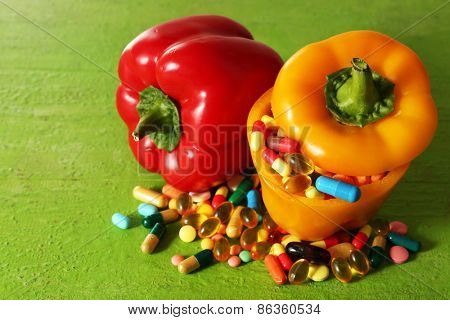 Orange pepper and colorful pills, on wooden background