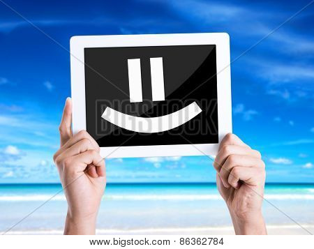 Tablet pc with text Smiley Face with beach background