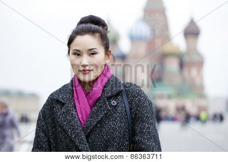 Portrait of a beautiful young asian woman in a gray coat on a red square, Moscow Russia