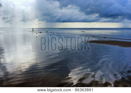 A Man Walks On The Beach With Reflection Of Clouds In The Sea