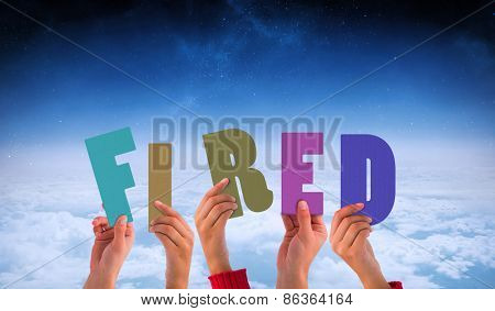 Hands holding up fired against white clouds under blue sky