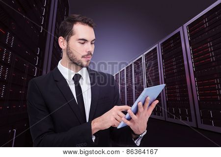 Cheerful businessman touching digital tablet against server hallway