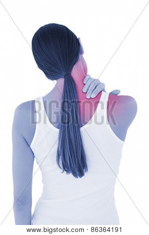 Rear view of a casual young woman suffering from neck ache over white background