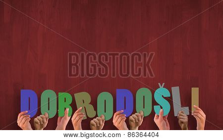 Hands holding up dobrodosli against wooden planks