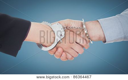 Business people in handcuffs shaking hands against blue