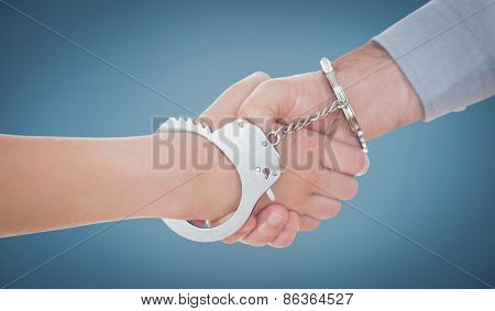 Handcuffed business people shaking hands against blue