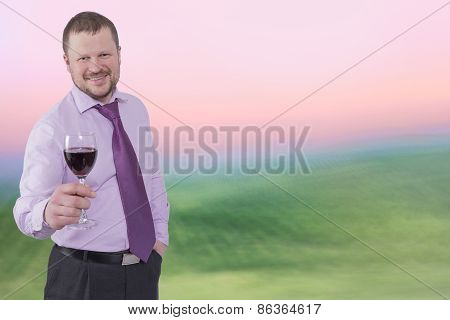 Businessman holding glass of wine with sunrise background