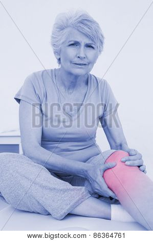 Portrait of a senior woman with a painful knee sitting on examination table