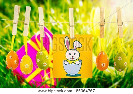 easter bunny against pink gift with easter egg and yellow tulip
