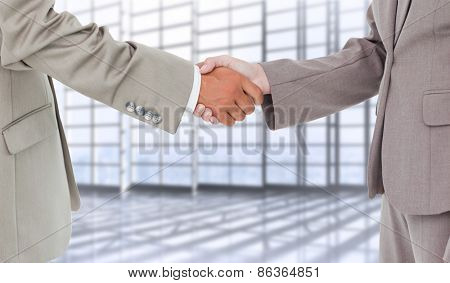 Side view of shaking hands against room with large window overlooking city