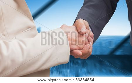 Business people shaking hands against room with large window looking on city