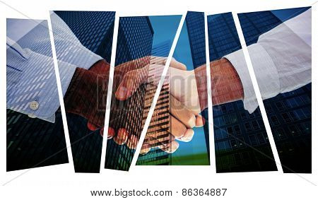 Close-up shot of a handshake against low angle view of skyscrapers