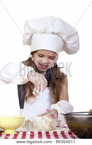 Portrait of a little girl in a white apron and chefs hat knead the dough in the kitchen, isolated on a white background