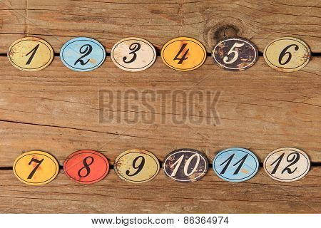 Vintage oval shaped wooden number buttons on a weather wooden table.
