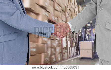 Side view of shaking hands against forklift machine in warehouse