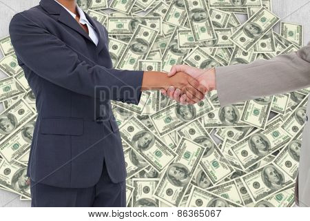 Side view of hands shaking against pile of dollars