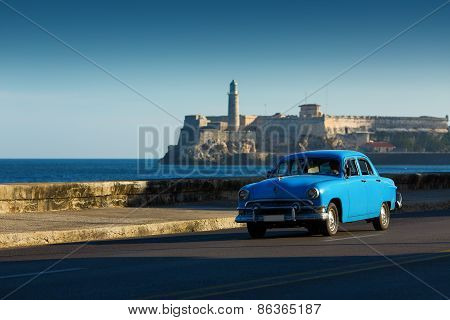 Old Classic Car On Street Of Havana With Ocean And Lighthouse In Background