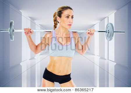 Strong female crossfitter lifting barbell behind head against digitally generated room
